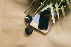 Summer vacation phone book sunglasses palm leaves chaise lounge. Phone with book, sunglasses and palm leaves on an old chaise lounge. Summer vacation concept stock images