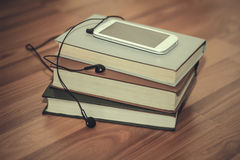 Phone on books. Knige.Muzyka mobile phone, reading, calm Stock Images