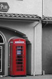 Phone booth. Red english phone booth on a sidewalk by a pub Royalty Free Stock Images