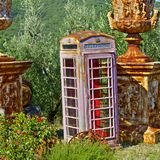 Phone Booth in Junk Shop. Old looking public phone and ancient things in the flea-market. Junk shop with phone booth in the midst of olive grove in Italy Royalty Free Stock Images