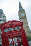 Phone booth in london. Red classic phone booth box with London landmark Big Ben in background Royalty Free Stock Photography