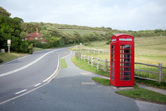 Phone booth and road on hills. Red phone booth on the hills against road and fields Royalty Free Stock Photo