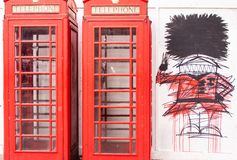 A phone box with graffiti of a foot guard stock photo
