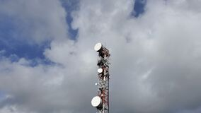 Phone broadcasting communication antenna tower over cloudy blue sky,electromagnetic waves pollution