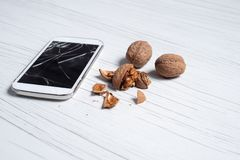 Phone with broken glass and the walnuts royalty free stock photos
