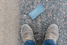 Phone with broken screen on asphalt. Someone dropped device royalty free stock photography