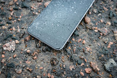 Phone with broken screen on asphalt Stock Photos