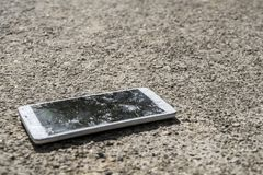 Phone with broken screen on asphalt. Someone dropped device. Royalty Free Stock Photography
