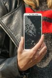 Phone with a broken screen in a female hand.  royalty free stock photography