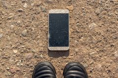 Phone with broken screen on ground. Someone dropped device. Phone with broken screen on ground at feet. Someone dropped device royalty free stock images