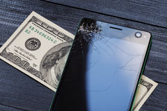 Phone with a broken screen, and the money needed for its repair Stock Image