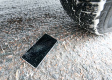 Phone with broken screen on snow in car trails Stock Photos