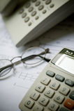 Phone and calculator. Desk phone ,glasses , calculator and draft Stock Photos
