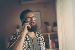 Phone call. Cheerful young man having phone conversation on his smart phone Stock Photo