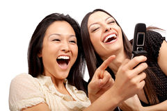 Phone call fun. Girlfriends laughing at something on their phone Stock Photo
