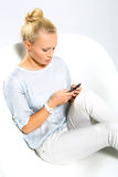 Phone Call. Girl writes a text message. Blonde talking on mobile phone while sitting on a stylish white chair Royalty Free Stock Images