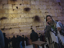 A phone call from the holy place. A religious man dressed with his prayer shawl making a phone call from the Wailing Wall in Jerusalem, the most holy place for Stock Photography