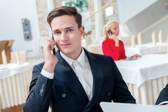 Phone call. Two successful and confident businessman sitting at. The table in a business office in full costume in the office and working at a laptop and Royalty Free Stock Photos
