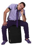 Phone Call. Young man sitting on a suitcase and using his mobile phone, isolated against a white background Royalty Free Stock Photo