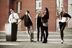 Young fashion people calling on cell phones in city street Royalty Free Stock Images