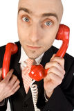 Phone calls. A businessman handling two phone calls at the same time, listening attentively to two red receivers stock images