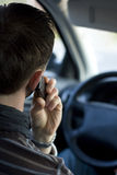 Phone in car. Man phoning in the car while driving royalty free stock image