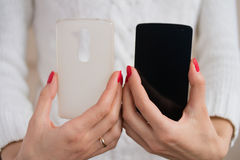 The phone and case for the phone in female hands. A girl holds in hands with bright red manicure mobile phone and phone case Stock Photography