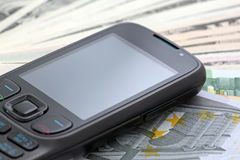 Phone on cash. Mobile phone on a cash (euro and dollars Stock Photo