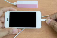 Phone charger with power bank on desk Royalty Free Stock Images