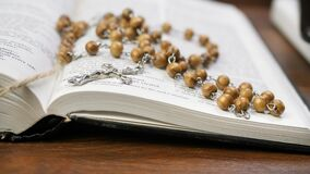 Phone charging from power bank and open holy bible with beads and cross on brown wooden table