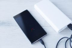 The phone is charging with Power bank stock photo