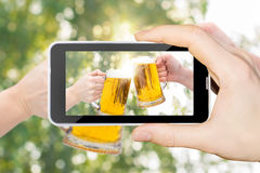 On the phone the Clinking Beer glasses on blurred background. Stock Image