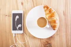 Phone, coffee and croissant Stock Photos