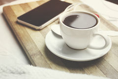Phone and coffee. Phone and cup of coffee on the bed Stock Images