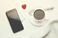 Phone and coffee. Phone and cup of coffee on the bed Stock Photos