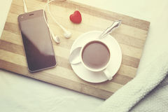 Phone and coffee. Phone and cup of coffee on the bed Royalty Free Stock Images