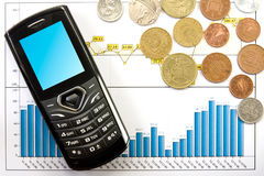 Phone  and coins over  business chart Royalty Free Stock Photos