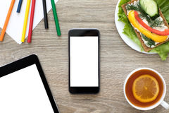 Phone and computer tablet with isolated screen in cafe Stock Photography