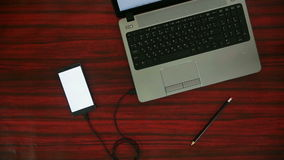 Phone connected to a laptop on a power strip through a cable and adapter. Person connecting smartphone to a laptop through a USB cable stock footage