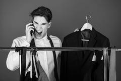 Businessman at wardrobe hanger with phone, shouting angry man royalty free stock photo