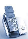 Phone In Cradle. Modern wireless  DECT phone in cradle over blue background Stock Photography