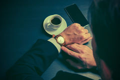 Phone and a cup of coffee in the hands of a businessman in dark colors Royalty Free Stock Image