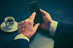 Phone and a cup of coffee in the hands of a businessman in dark colors Royalty Free Stock Images