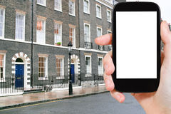 Phone with cut out screen and London house. Travel concept - hand holds smartphone with cut out screen and London apartment house on background Stock Photo