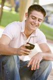 phone den mobila det fria för pojke sittande tonårs- använda Royaltyfri Foto