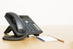 Phone on desk with notepad on wooden desk Royalty Free Stock Photography