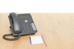 Phone on desk with notepad on wooden desk Royalty Free Stock Photos