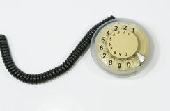 Phone dialer vintage. Vintage disc shaped phone dialer attached to a curled up communications cable stock image