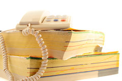 Phone directories. Home telephone on top of phone directories Royalty Free Stock Image