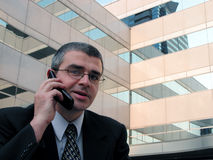 Phone discussion. Business man talking to the phone in front of a conference building Stock Image